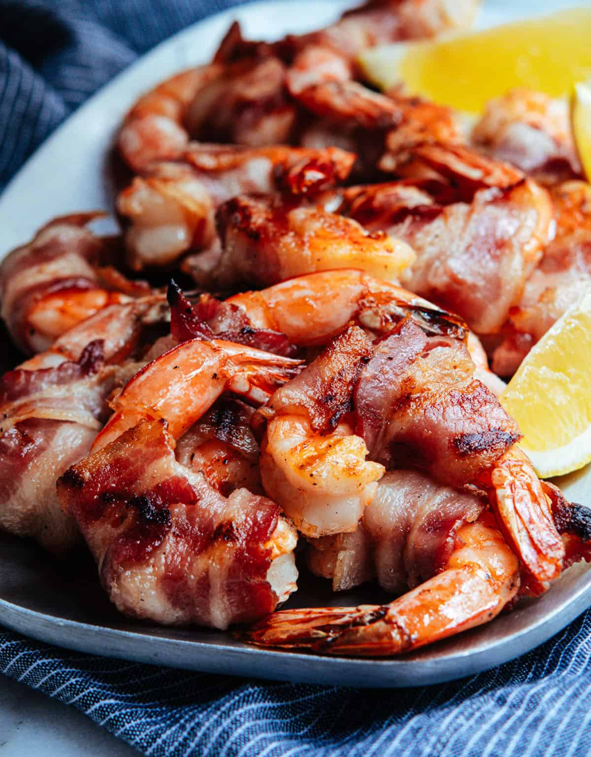 Grilled Bacon Wrapped Shrimp served on a stainless steel platter.