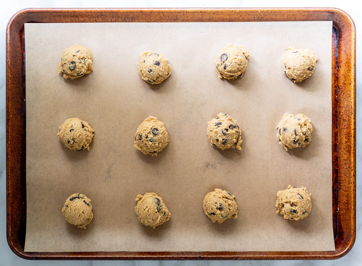 Oat Flour Chocolate Chip Cookie dough scooped onto parchment lined baking sheet.