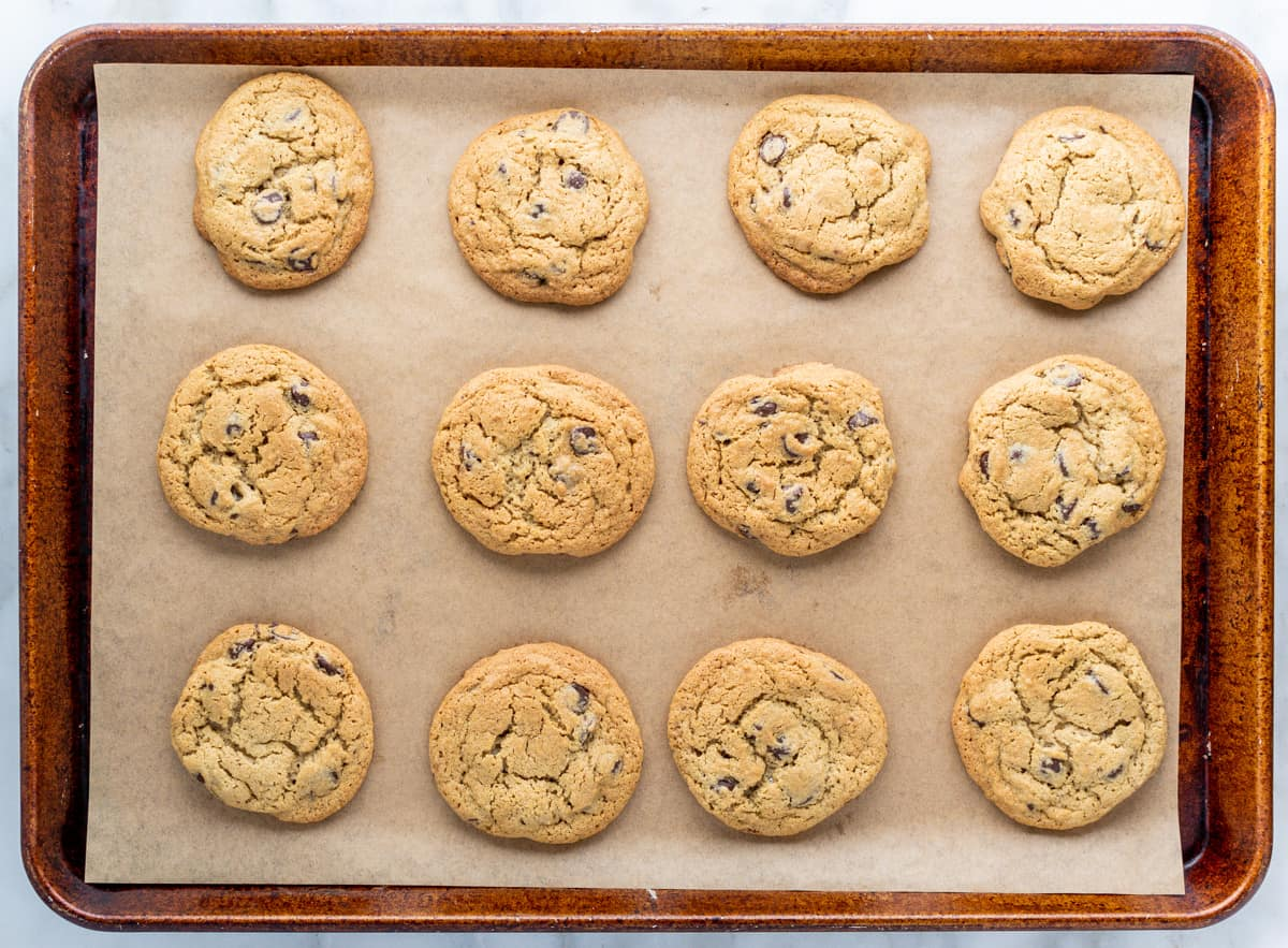 Oat Flour Chocolate Chip Cookies on a parchment lined baking sheet.