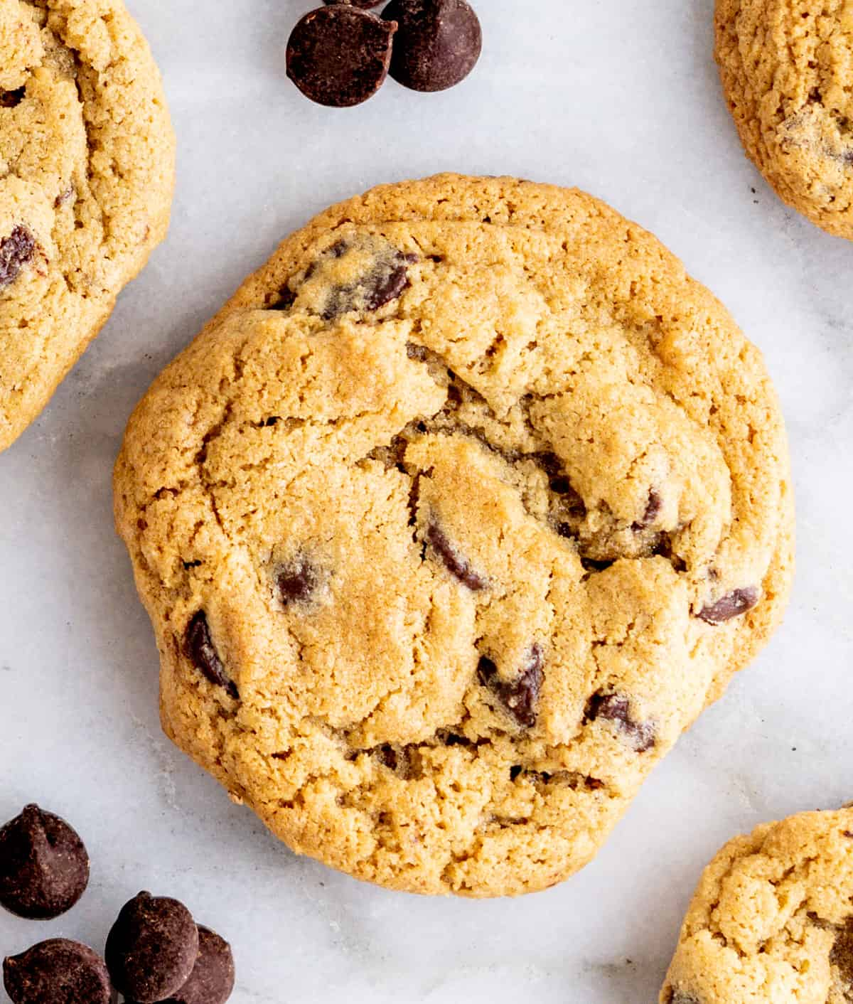 Oat Flour Chocolate Chip Cookies on a white marble board with scattered chocolate chips.