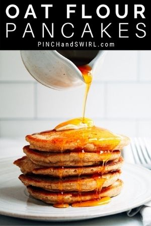 Pouring syrup over stacked Oat Flour Pancakes.