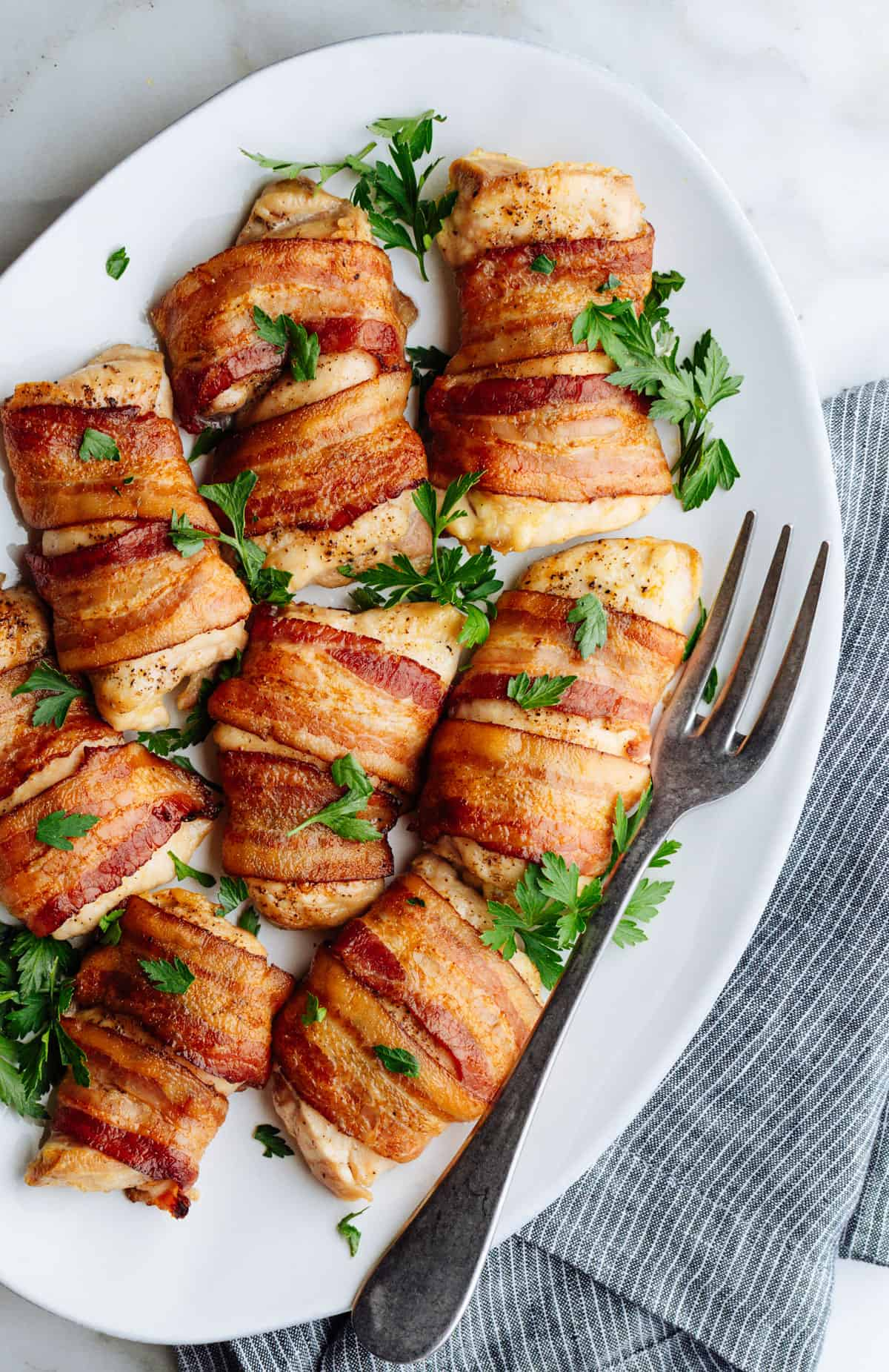 Bacon Wrapped Chicken Thighs served on a white oval platter photographed from above.