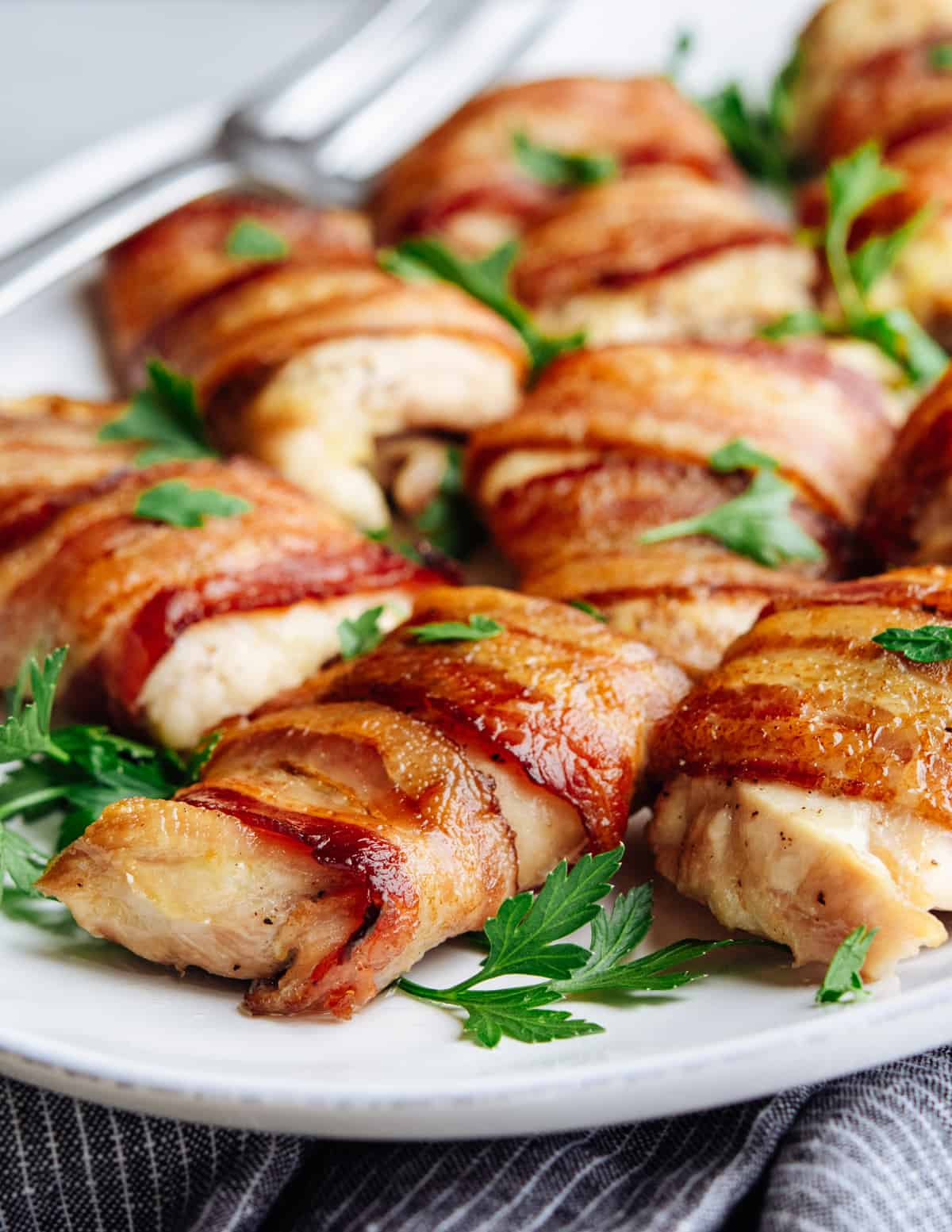 Bacon Wrapped Chicken Thighs served on a white oval platter.