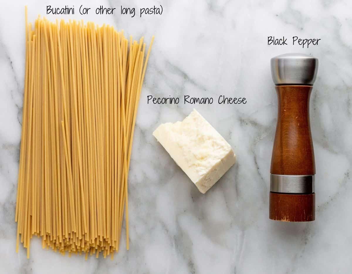 Bucatini Cacio e Pepe Ingredients on a white marble board.