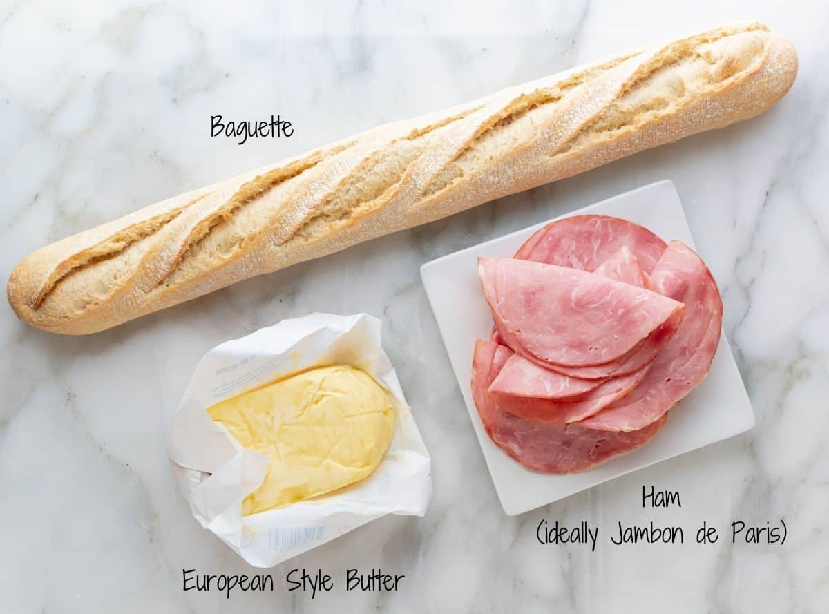 Jambon Beurre Sandwich Ingredients on a white marble board.