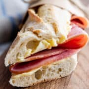Brown paper parchment wrapped Jambon Beurre sandwich on a wooden board.