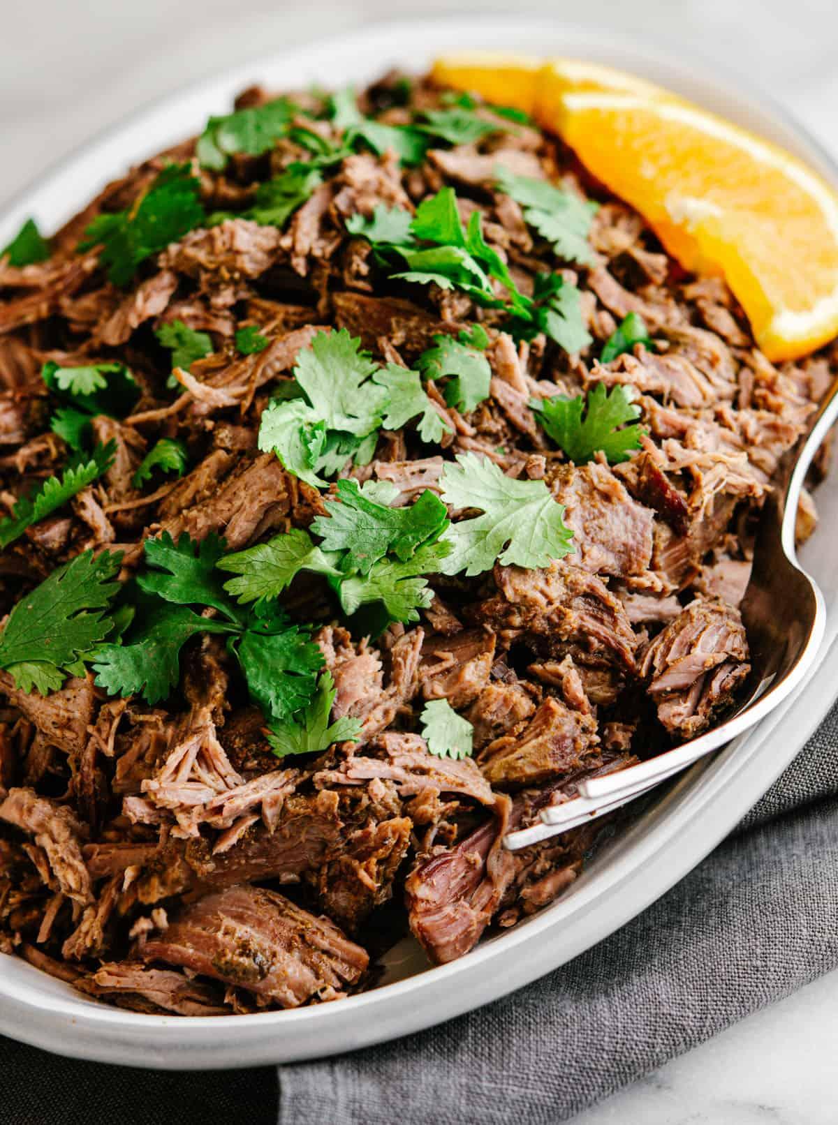 shredded lamb barbacoa served on an oval platter.