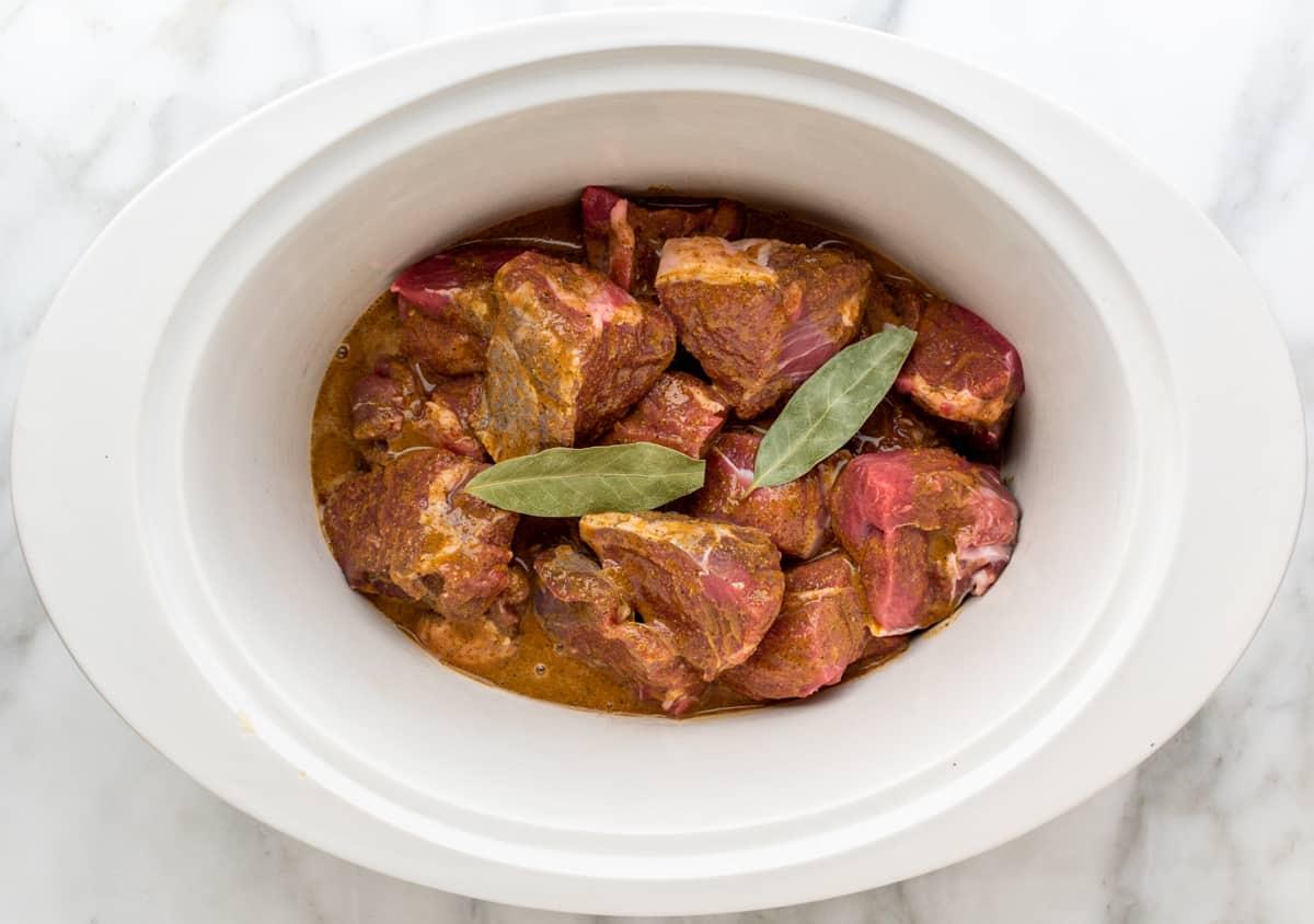 raw Lamb Barbacoa ingredients in slow cooker.