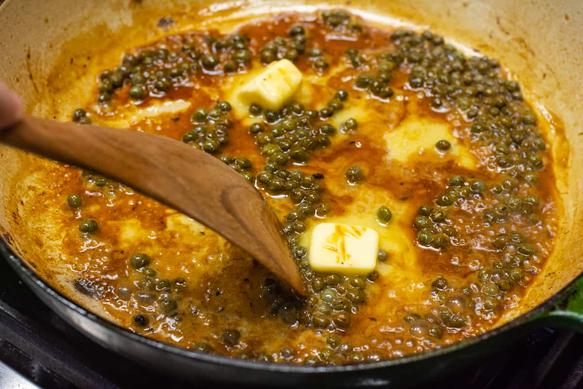 stirring butter into piccata sauce in skillet.